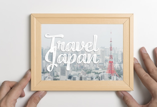 Hand holding travel japan tokyo poster in photo frame Premium Photo