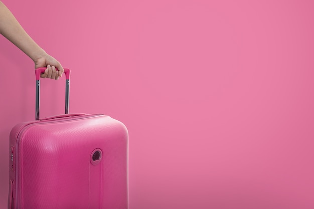 Hand holding traveler pink suitcase or cabin size luggage on pink Premium Photo