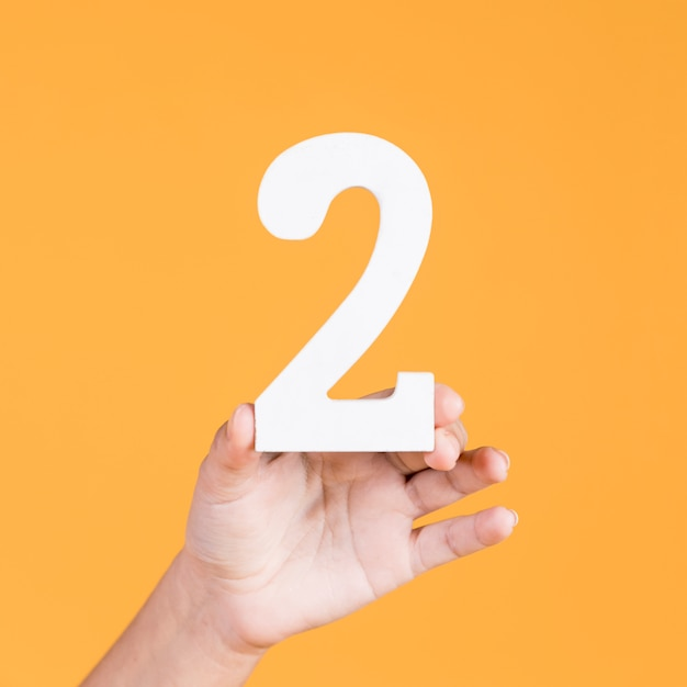Hand holding up the number two over yellow background Premium Photo