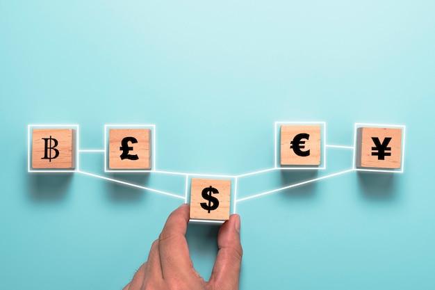 木製の立方体に米ドル記号の印刷画面を持っている手と元の円のユーロと英ポンドとのリンク。外貨両替と外国為替の概念。 Premium写真