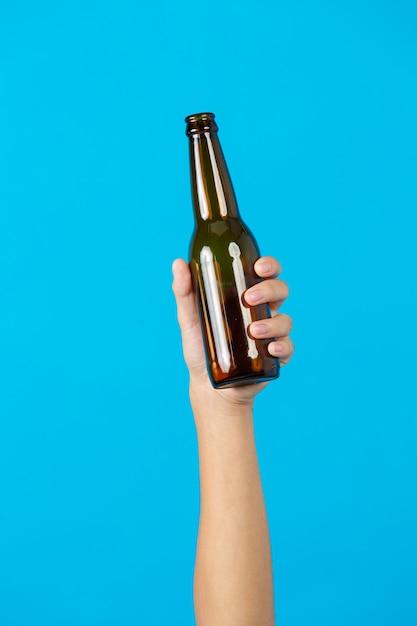 Mano che tiene la bottiglia usata su sfondo blu Foto Gratuite
