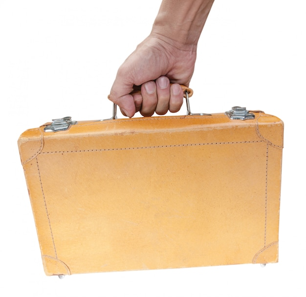 Hand holding vintage brown suitcase isolated on white background Premium Photo
