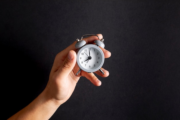 Hand holding a vintage little clock Free Photo