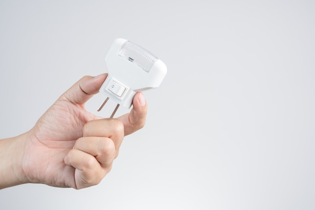 Hand holding wall led light plug, and electric outlet Premium Photo