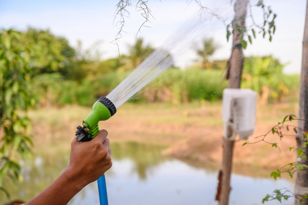 Hand holding water sprayer with watering Premium Photo