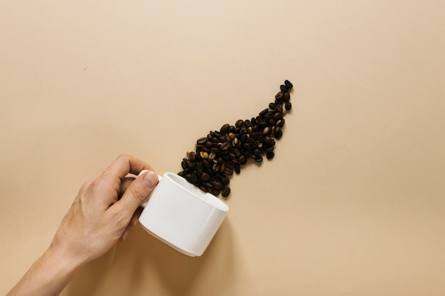 Hand holding white cup with coffee beans Free Photo