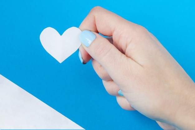 Hand holding a white heart on a white and blue background Premium Photo