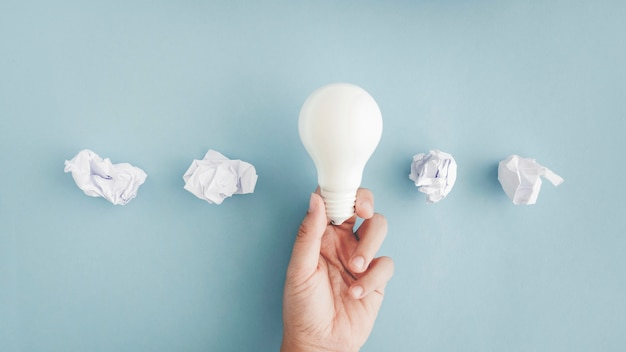 Hand holding white light bulb with crumpled paper balls on gray background Free Photo