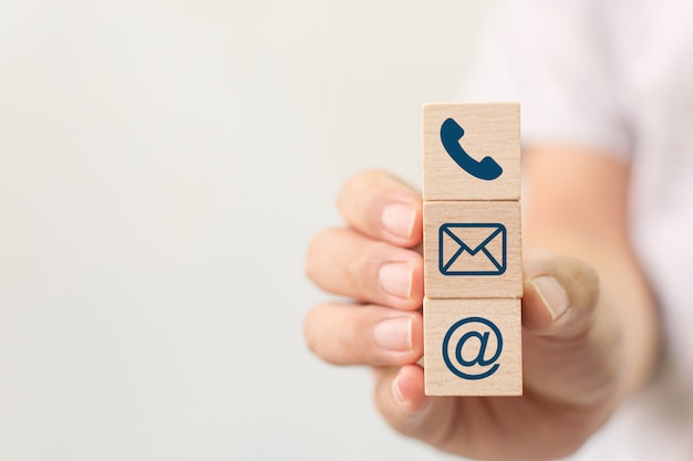 Hand holding wooden block cube symbol telephone, email, address. website page contact us or e-mail marketing concept Premium Photo