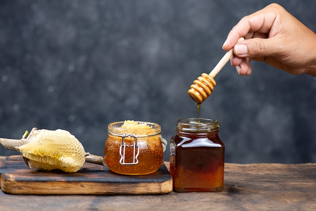 Hand holding wooden honey dipper Premium Photo