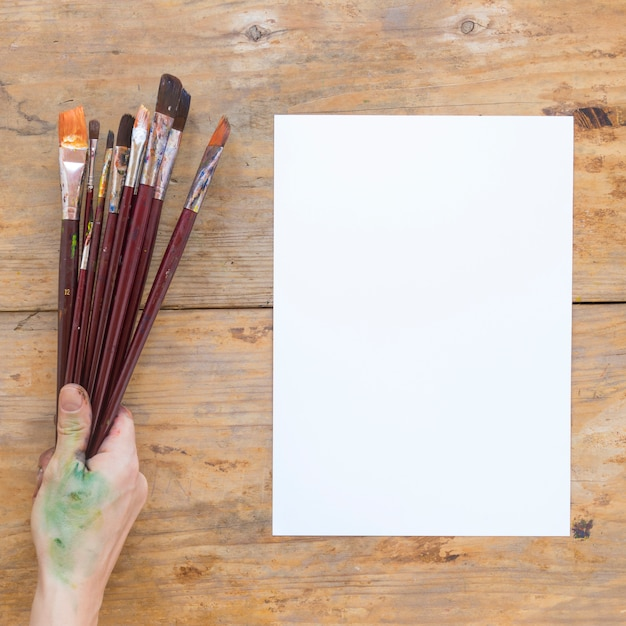 Hand holding wooden paint brushes near white paper Free Photo