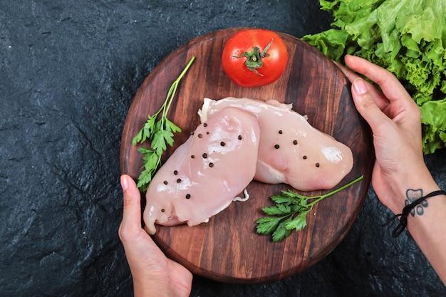 Рука деревянная тарелка сырого куриного филе с зеленью на темном столе. Бесплатные Фотографии