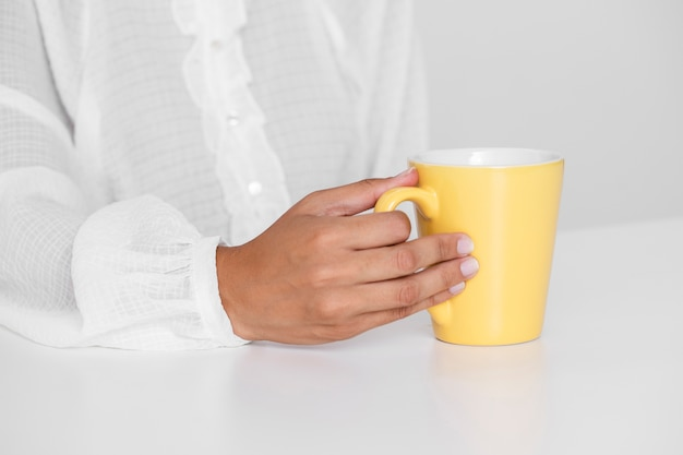Hand holding yellow cup on a table Free Photo