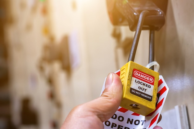 Hand holding yellow key lock and tag for process cut off electrical Premium Photo