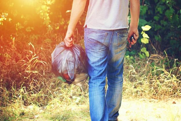 Hand holds against forest full garbage black plastic bag Premium Photo