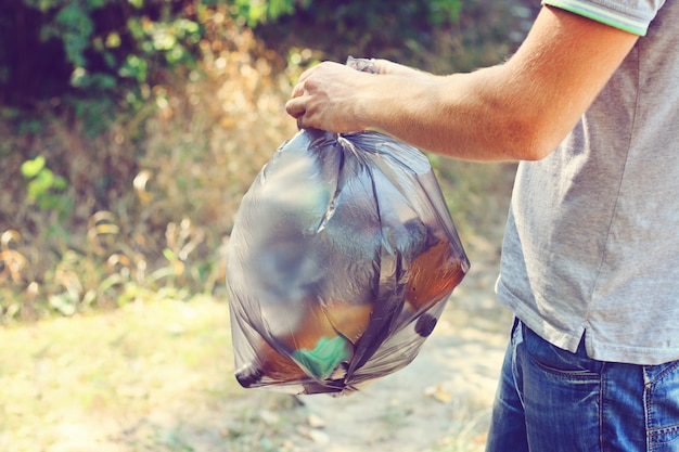 Hand holds against a forest full of garbage a large black plastic bag, a summer day Premium Photo