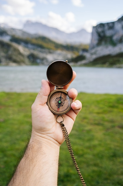 A hand holds a compass in a mountain and lake landscape Premium Photo