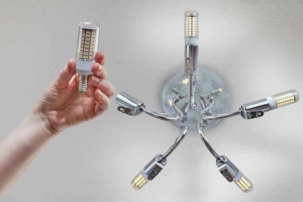 손은 크롬 천장 샹들리에에 설치하기 전에 가정용 Led 옥수수 램프를 보유합니다. 프리미엄 사진
