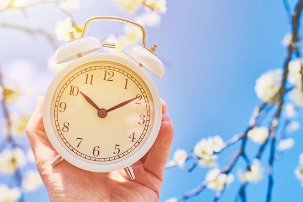 手は青い空と咲く植物に対してビンテージの目覚まし時計を保持しています。 Premium写真