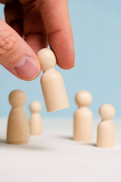 A hand holds a wooden figurine on a blue background. team building concept. close up. Premium Photo