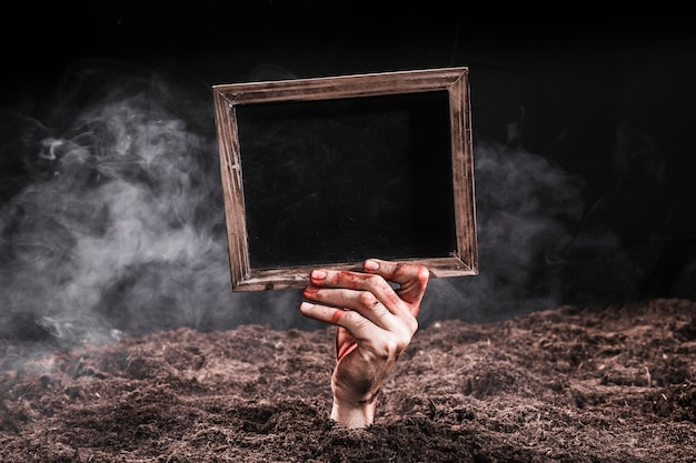 Hand in blood sticking out of ground and holding black sign Free Photo