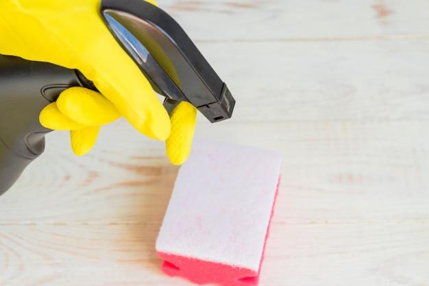黒のプラスチックスプレー洗剤ボトルを保持している黄色のゴム手袋で手します。家庭用化学物質。クリーニング製品。 Premium写真