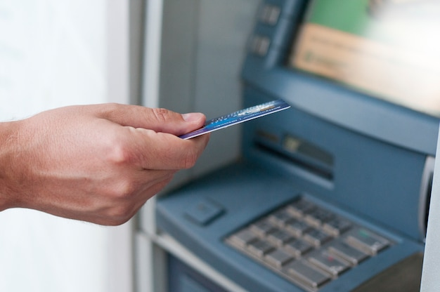 Hand inserting atm card into bank machine to withdraw money. businessman men hand puts credit card into atm Free Photo