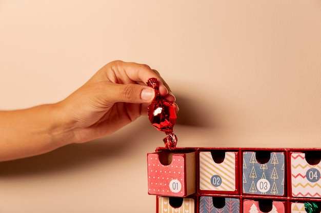 Hand inserting one candie in advent calendar Free Photo