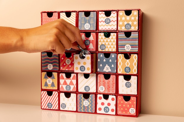 Hand inserting small candie in advent calendar Free Photo