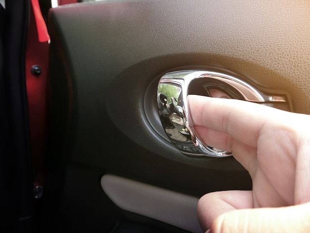 The hand is opening the door handle inside the car. Premium Photo