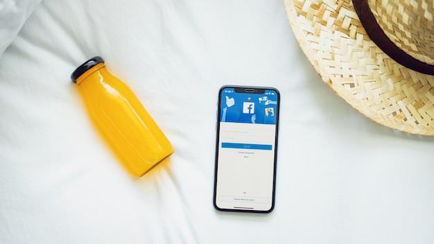 Hand is pressing the facebook screen on apple iphone x ,social media are using for informa Premium Photo