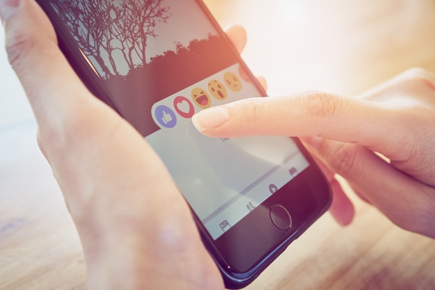 Hand is pressing the facebook screen smartphone Premium Photo