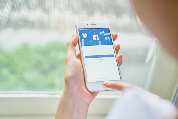 hand is pressing the Facebook screen Premium Photo