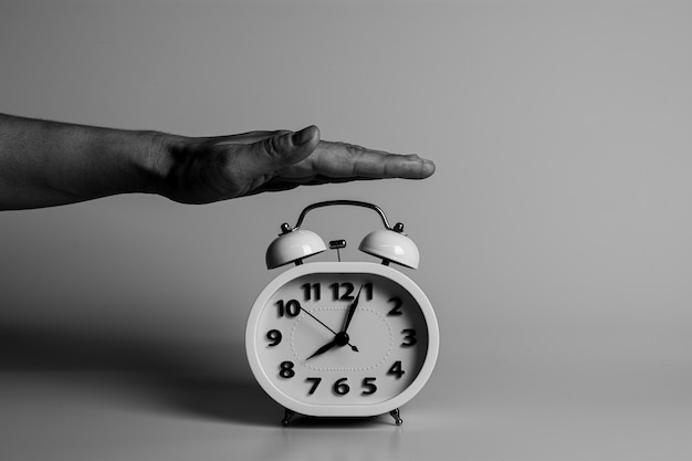 Hand is slapping for destroy and stop a alarm clock. Premium Photo