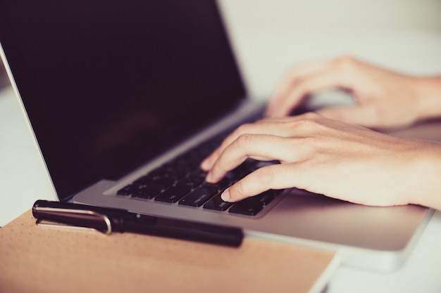 Hand on laptop keyboard with clean background, work at home concept Premium Photo