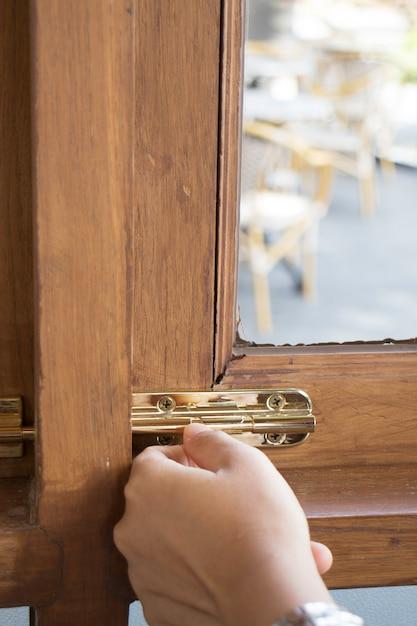 Hand locked on wooden frame window Premium Photo
