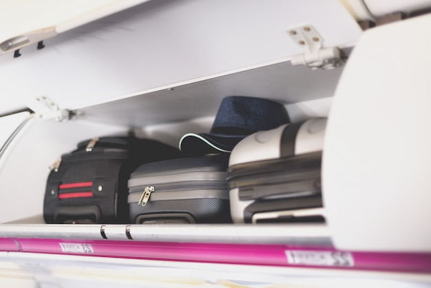 Hand-luggage compartment with suitcases in airplane. Premium Photo