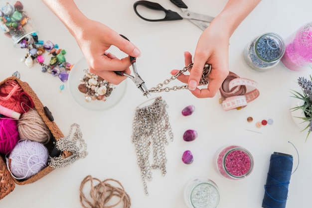 Hand making and cutting the metallic chain on white desk with beads Free Photo