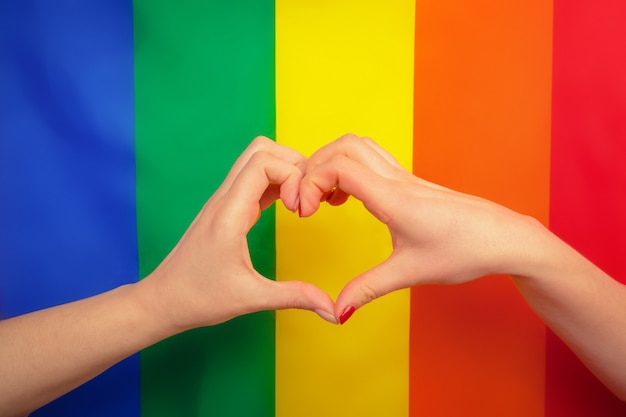 Hand making a heart sign with gay pride lgbt rainbow flag Premium Photo