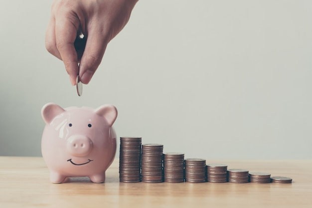 Hand of male or female putting coins in piggy bank with money stack Premium Photo