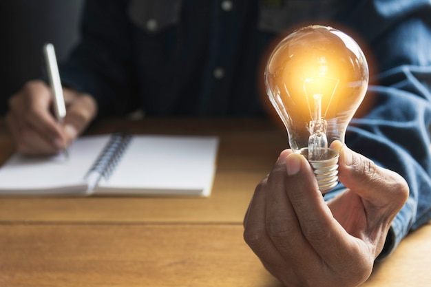Hand of male holding a light bulb and copy space for accounting Premium Photo