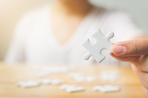 Hand of male trying to connect pieces of white jigsaw puzzle on wooden table Premium Photo