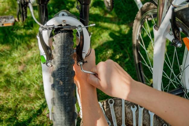 手マン屋外、クローズアップの手で自転車の車輪を修正します。 Premium写真