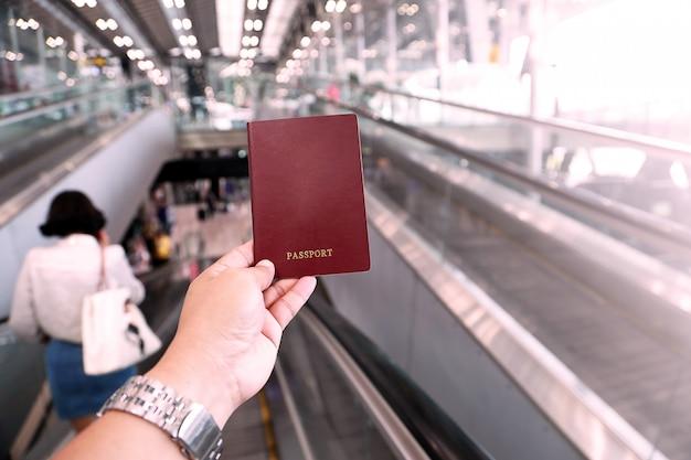 Hand of man holding passport at airport, plastic pink tone. Premium Photo