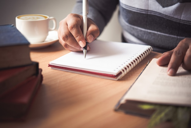 The hand of a man holding a pen and taking notes in a notebook. Premium Photo