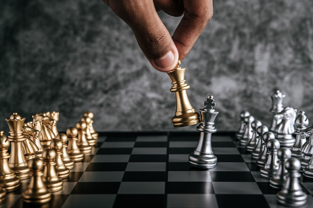 Hand of man playing chess for business planning and comparison of metaphor, selective focus Free Photo