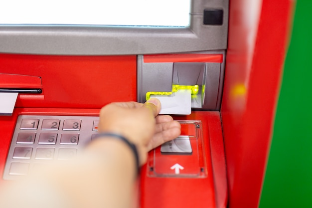 Hand of man using an atm machine with credit card. Premium Photo
