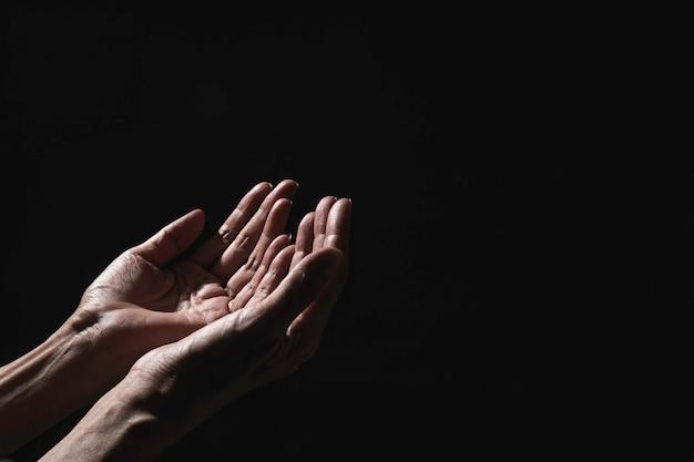 Hand of man while praying for religion. Premium Photo