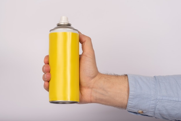 Hand men, holding a yellow spray paint. without an inscription on a white background. mock up Premium Photo