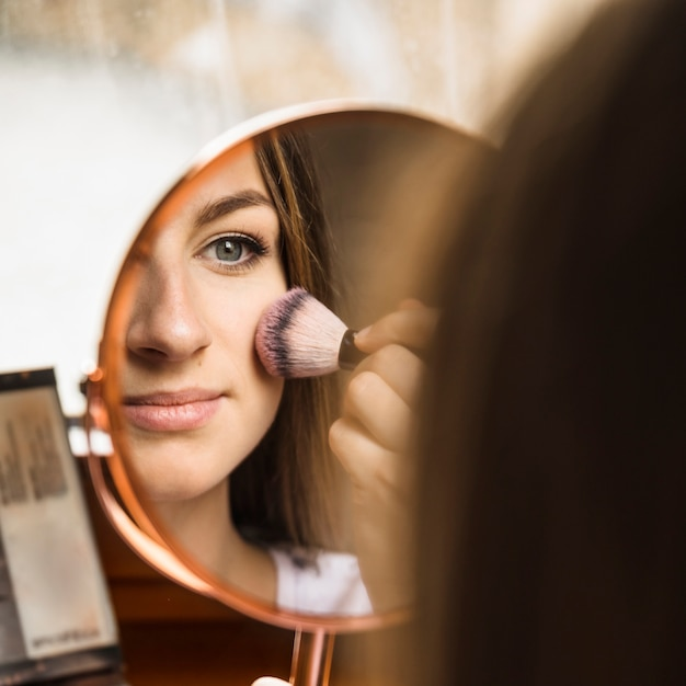 Hand mirror with reflection of woman applying blusher on her face Free Photo
